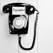 Retro phone with a note to give feedback — Stock Photo
