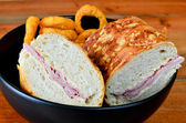 Cheese bread ham baguette with onion rings — Stock Photo