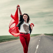 Beautiful girl on road with fabric opening wide from wind — Stock Photo