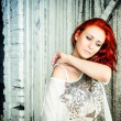 Foto Stock: Beautiful girl with red hair outdoor against wooden doors
