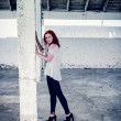 Foto Stock: Beautiful girl with red hair outdoor in thrown old warehouse