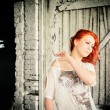 Beautiful girl with red hair outdoor against wooden doors — Stock fotografie #32139885