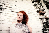Beautiful girl with red hair outdoor against brick wall — Stock Photo