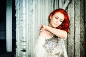 Beautiful girl with red hair outdoor against wooden doors — Stock Photo