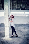 Beautiful girl with red hair outdoor in thrown old warehouse — Stock Photo