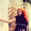 Beautiful girl with red hair outdoor against clay house — стоковое фото #32140829