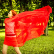 Stock Photo: Happy womin red rejoices to wind