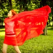 Happy woman in red rejoices to wind — Stock Photo