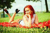Beautiful woman with red hair has rest in park — Stock Photo
