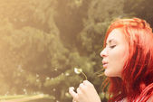 Beautiful woman with red hair blows into dandelion — Stock Photo
