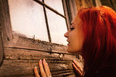 Woman curiously looks in window of old house — Stock Photo