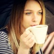 Womanl drinks fragrant coffee with pleasure under umbrella — Стоковая фотография