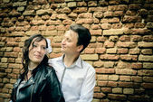 Unusual wedding couple near a brick wall — Stock Photo