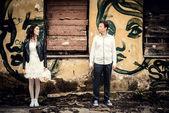 Unusual loving wedding couple near wall with graffiti — Stock Photo