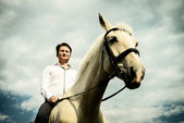 Unusual groom at wedding on white horse outdoors — Stock Photo