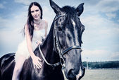 Unusual bride at wedding on black horse outdoors — Stock Photo