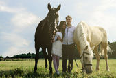 Wedding of unusual couple happy near horses — Stock Photo