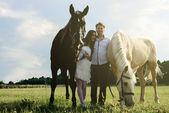 Wedding of unusual couple happy near horses — Stock Photo