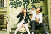 Unusual loving wedding couple near wall with graffiti thrown hou — Stock Photo