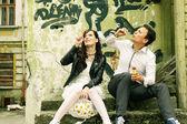 Unusual loving wedding couple near wall with graffiti thrown hou — Stock Photo