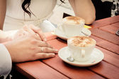 Unusual loving wedding couple in cafe drinks cappuccino — Stock Photo
