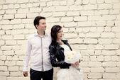Unusual wedding couple near a brick wall — Stock Photo
