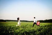Romantic couple of lovers in field runs towards each other — Stock Photo