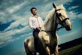 Unusual groom at wedding on white horse outdoors — Stok fotoğraf