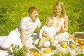 Família feliz com o filho e piquenique — Fotografia Stock