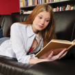 Foto Stock: Teenage girl reading book on sofa