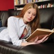 图库照片: Teenage girl reading book on sofa