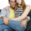 Juvenile couple snuggling on the sofa - Foto Stock