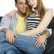 Juvenile couple snuggling on the sofa - Stockfoto