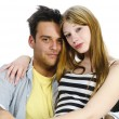 Juvenile couple snuggling on the sofa - Stock Photo