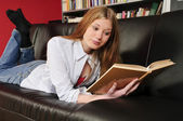 Teenage girl reading a book on the sofa — Stock Photo