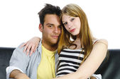 Juvenile couple snuggling on the sofa — Foto Stock