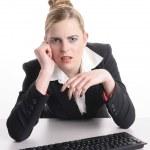 mujer joven sentada en la computadora molesta — Foto de Stock