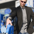 Young man with convertible at gas station - Stock Photo