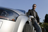 Successful businessman in front of his convertible — Stock Photo