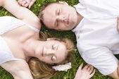 Liefde paar liggen in het gras — Stockfoto