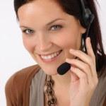 Friendly help desk woman smiling — Stock Photo #11375413