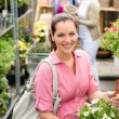 Garden centre woman hold white potted hibiscus - Stock Photo