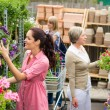 Woman taking potted plant at garden center — Stock Photo