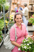 Garden centre woman hold white potted hibiscus — Stock Photo
