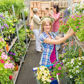 Woman shopping for flowers in garden shop — Stok fotoğraf