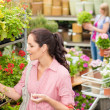 Woman choose potted flower in garden store — Stock Photo #12060026