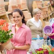 Garden centre woman hold red potted geranium - Foto de Stock