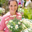 Woman hold potted flowers at garden centre — Stock Photo