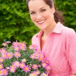 Female florist hold pink potted flower — Stock Photo