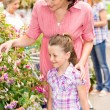 Garden centre child mother at plant market - Stock fotografie